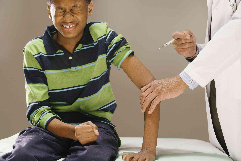 Teenage boy (12-13) bracing himself for injection