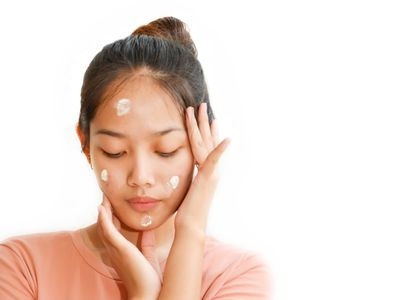 Close-Up Of Teenage Girl With Cream On Face Against White Background
