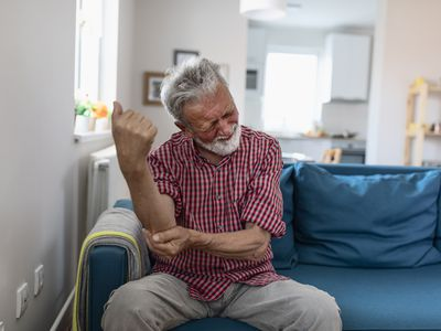 Man feeling elbow pain, chronic rheumatism