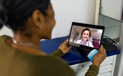 Woman having a telehealth visit with her doctor using digital tablet.