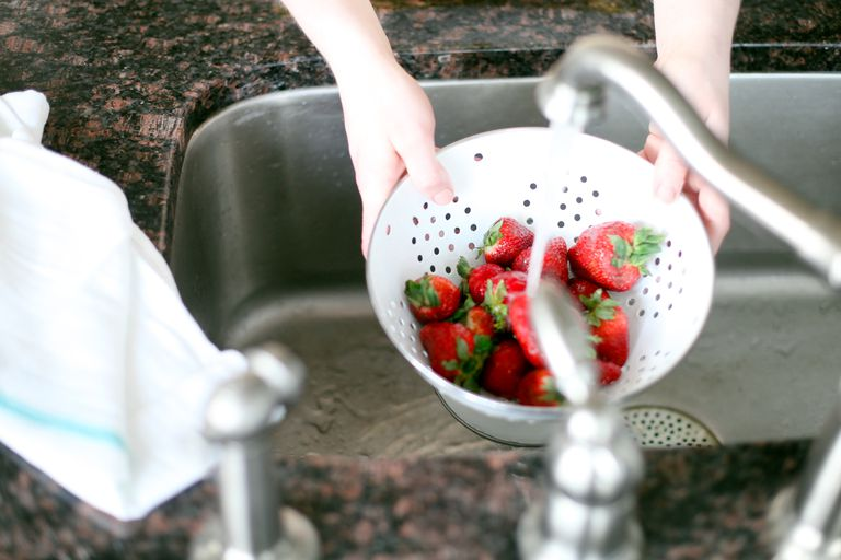 Washing strawberries in a strainer
