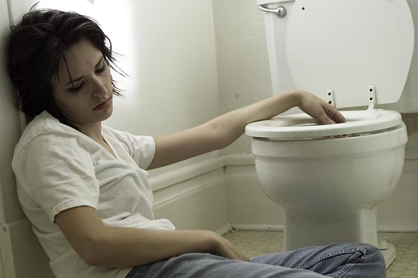 Sick young woman leaning on bathroom wall by toilet