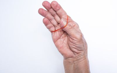 Senior woman's hand holding red elastic rubber band