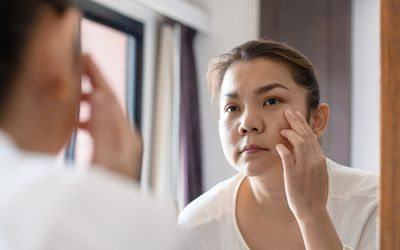 Woman in front of mirror with reflection - stock photo