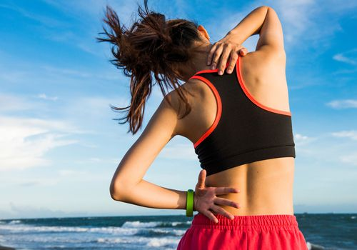 A woman suffering back pain after a workout by the ocean