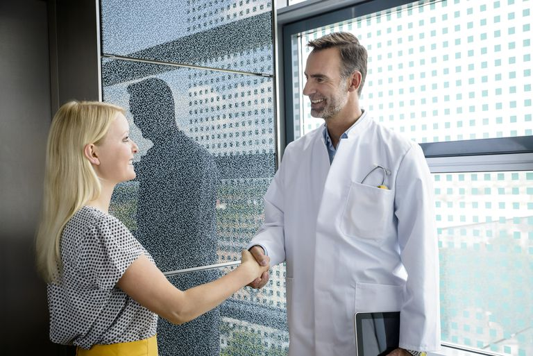 Senior doctor shaking patient's hand, smiling