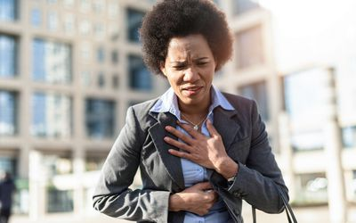 Woman holds chest and stomach and looks like she is in discomfort from heartburn