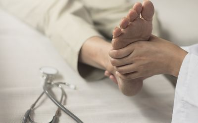 Heel Pain or plantar fasciitis concept. Hand on foot as suffer from inflammation feet problem of Sever's Disease or calcaneal apophysitis.