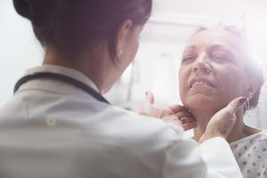Woman getting her thyroid checked by a doctor