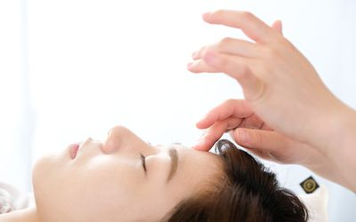 Woman receiving acupressure between the eyes at an acupuncture clinic - stock photo