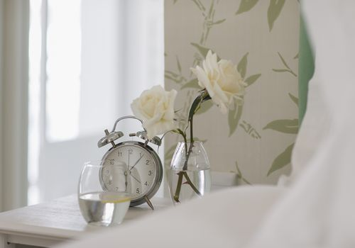 White roses, alarm clock and water glass on bedside table