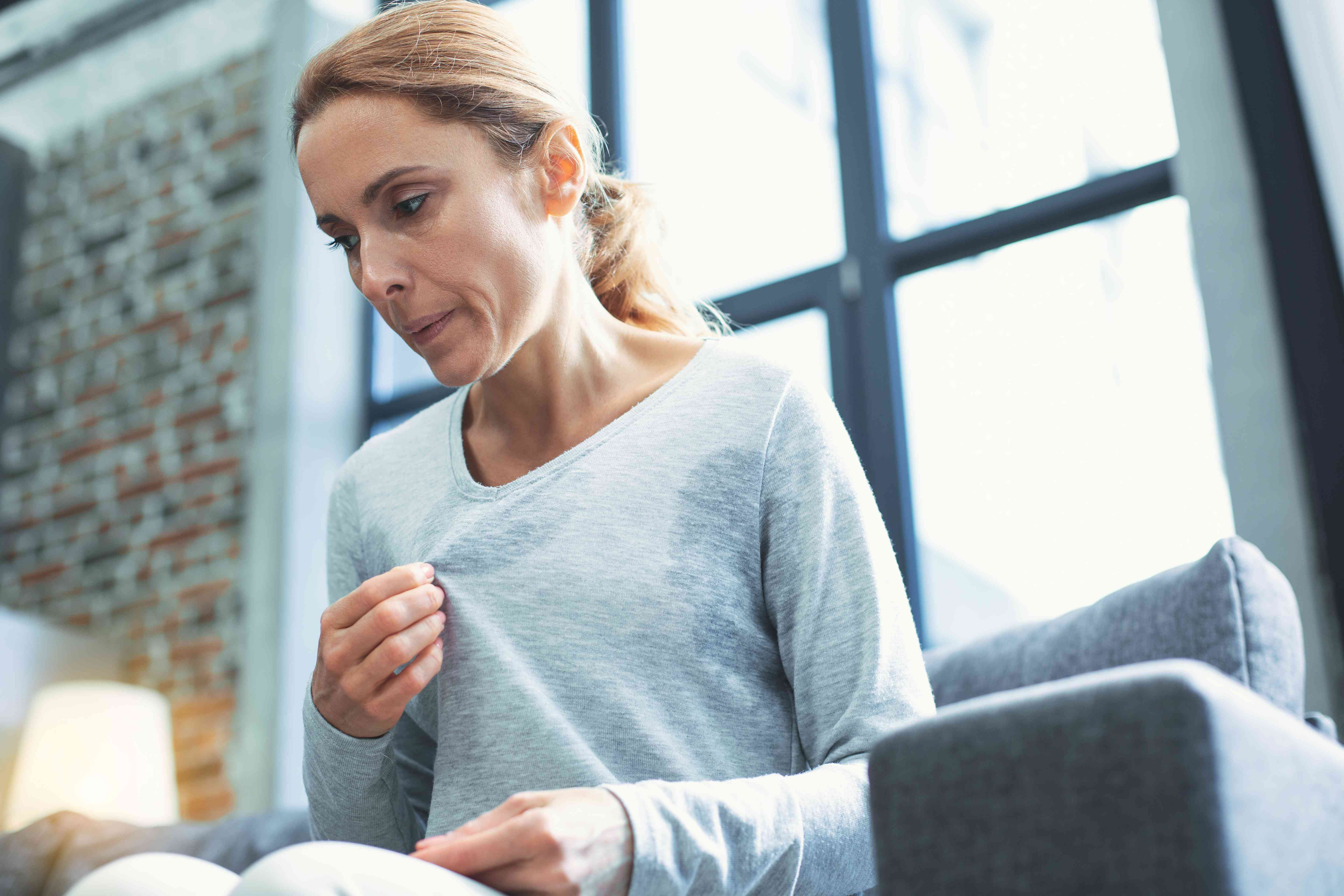 Exhausted mature woman entering menopause
