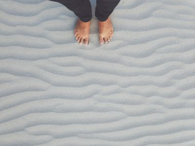 Looking down on feet standing on rippled sand