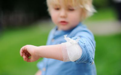Cute little boy looking on his elbow with applied bandage