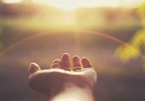 hand reaching out toward the sun representing letting go with cancer
