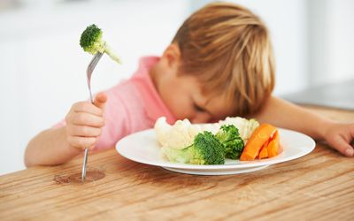 A cute young boy with his head on the table while holding a piece of broccoli on his fork.