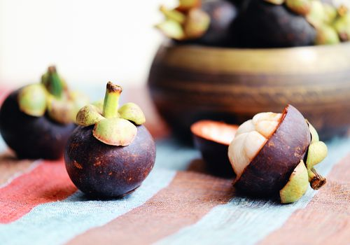 Mangosteens on a striped tablecloth with a wooden bowl in the background