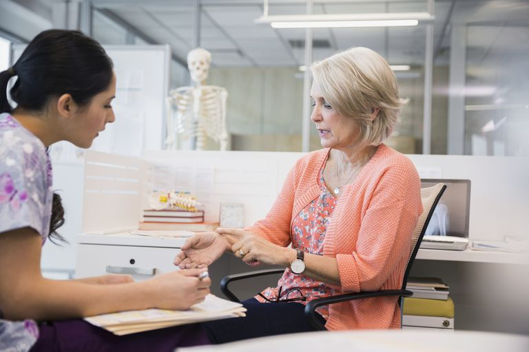 Patient explaining wrist pain to nurse in clinic