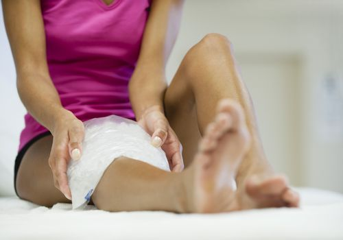 woman icing painful knee