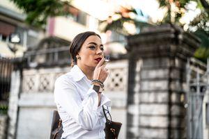 Businesswoman walking and smoking