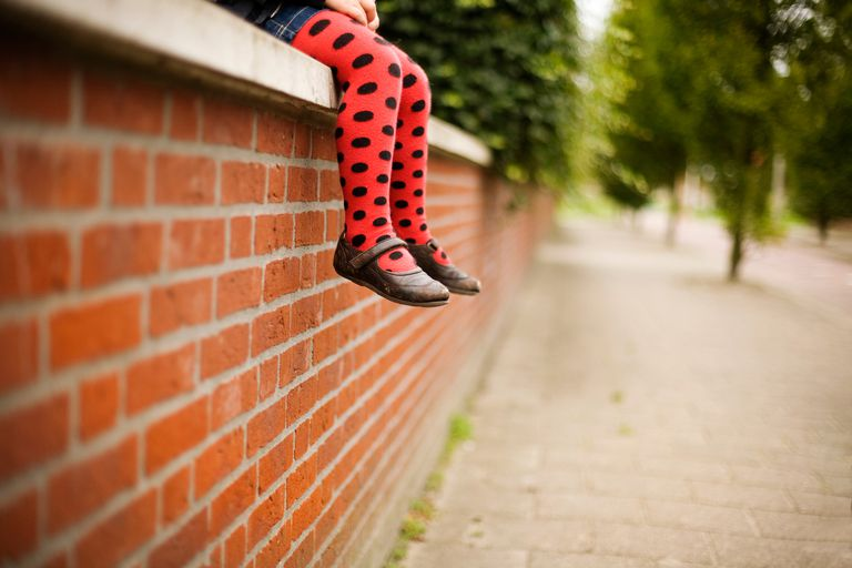 little girl sitting on a brick wall with the focus on her shoes