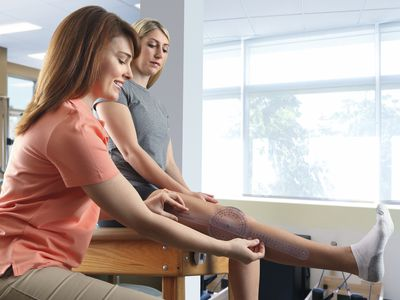 physical therapist helping patient with ACL knee rehab exercises