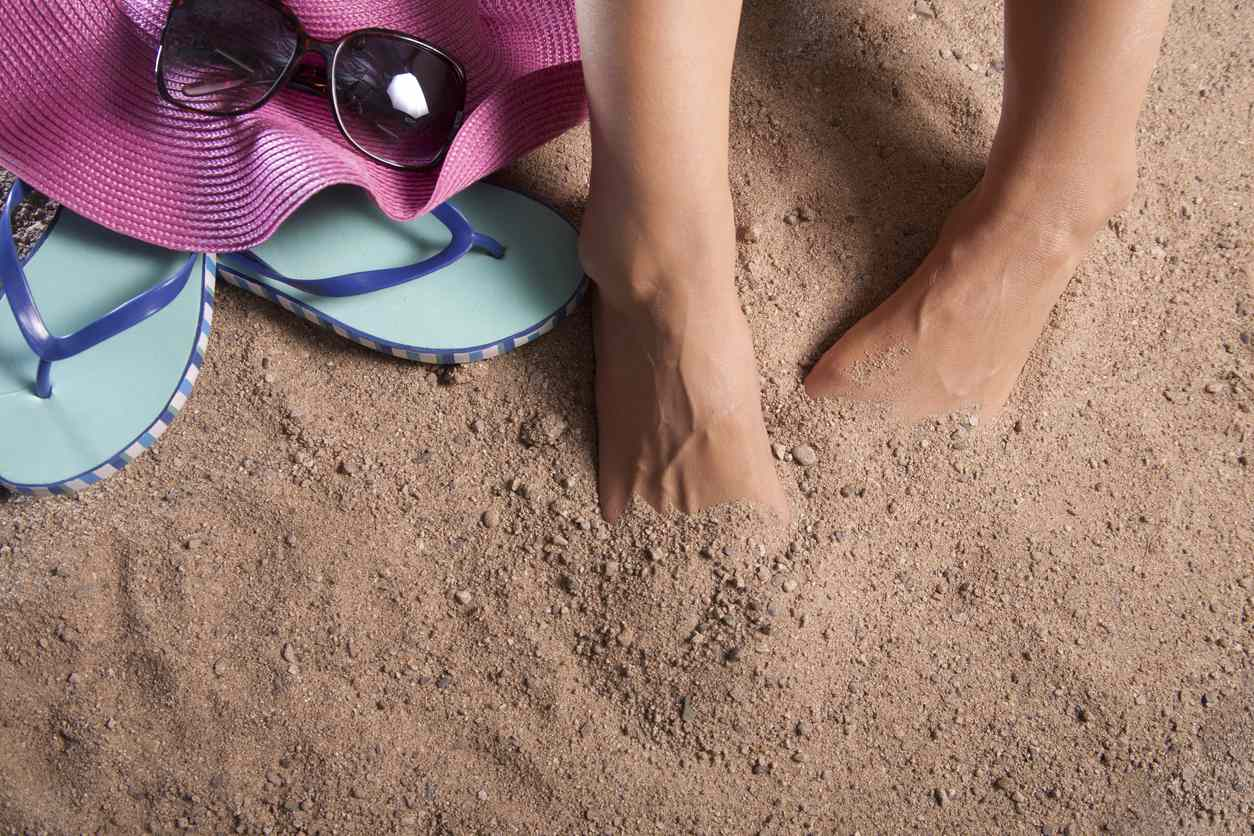 Pair of feet buried in the sand