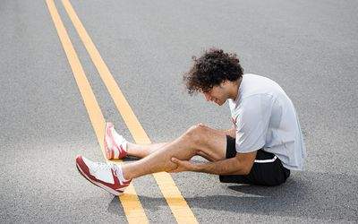 A runner with an injured leg sitting in the road
