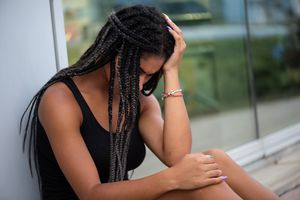 A black woman looking down and holding her head with a hand.