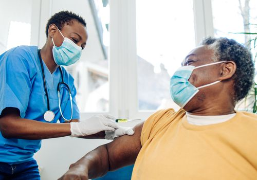 Black man wearing a mask receiving vaccine form medical professional