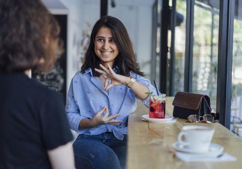 Woman doing sign language at cafe