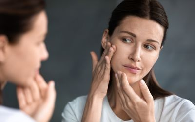 Close up unhappy woman looking at acne spots in mirror - stock photo