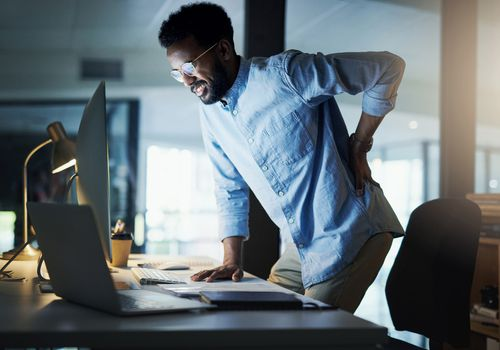 Shot of a young businessman experiencing back pain while working in an office at night
