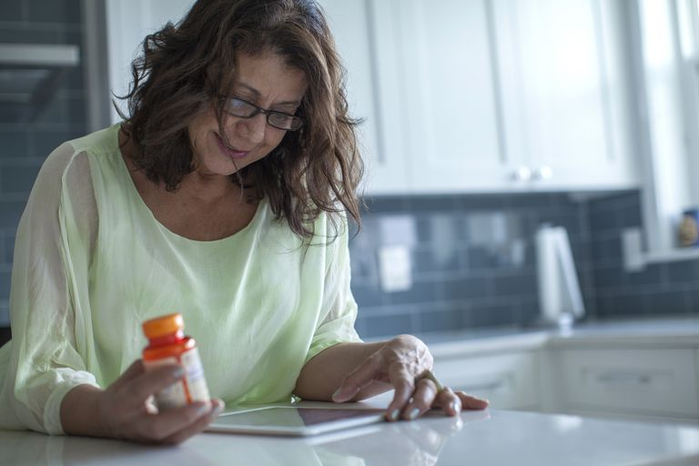 Woman holding pill bottle and using tablet