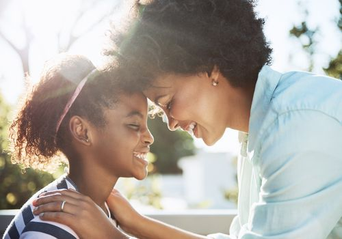 Shot of a cheerful young mother and her daughter putting their heads together while keeping their eyes closed