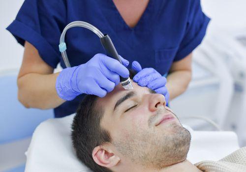 Midsection Of Dermatologist Examining Man At Hospital