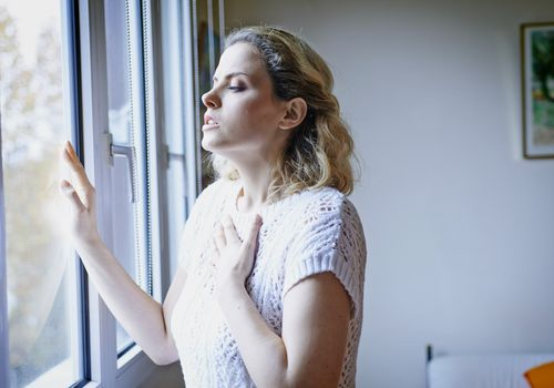 Woman with breathing difficulties next to window