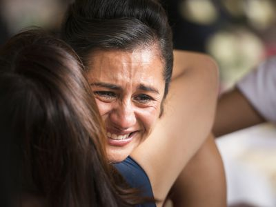 Hispanic women hugging and crying