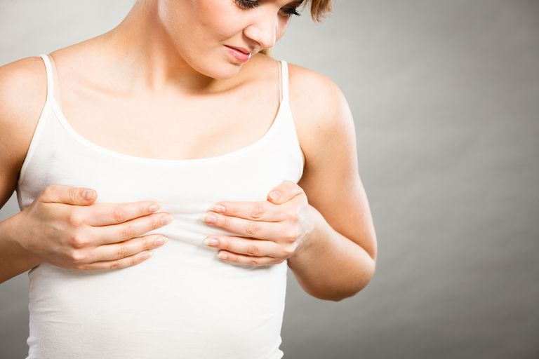 woman holding her breasts wondering what benign breast conditions mimic breast cancer