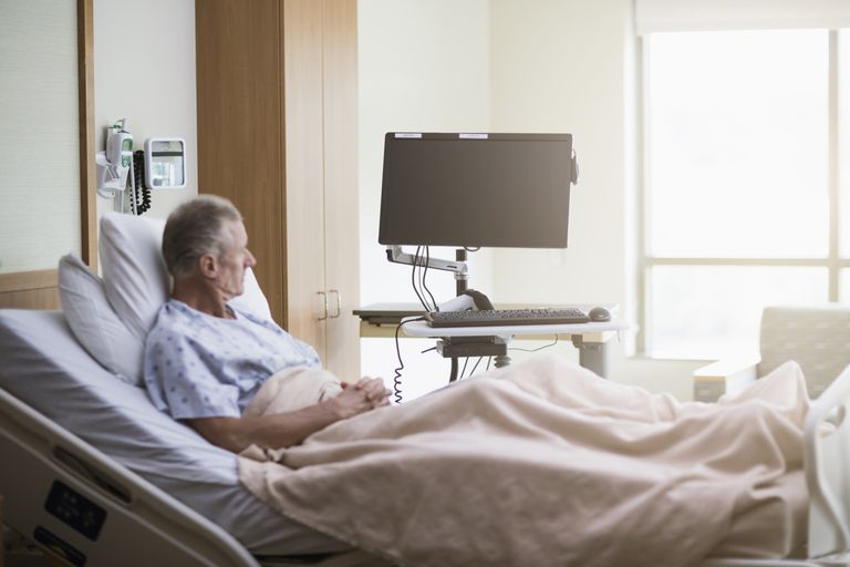 Man sitting in a hospital bed looking out the window