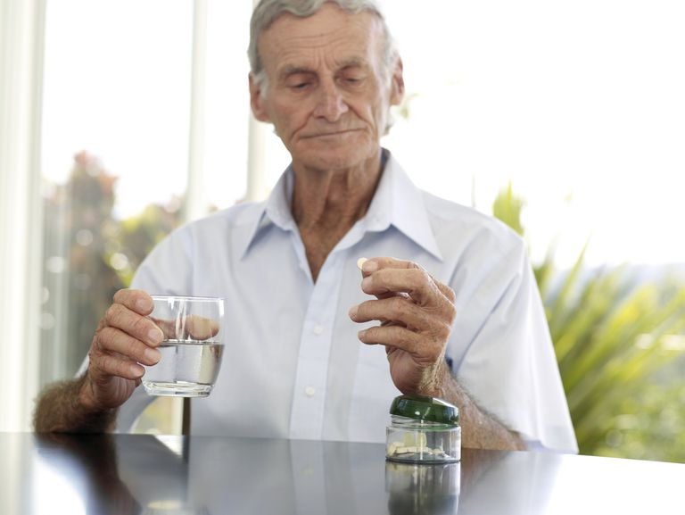 elderly man taking a pill with water