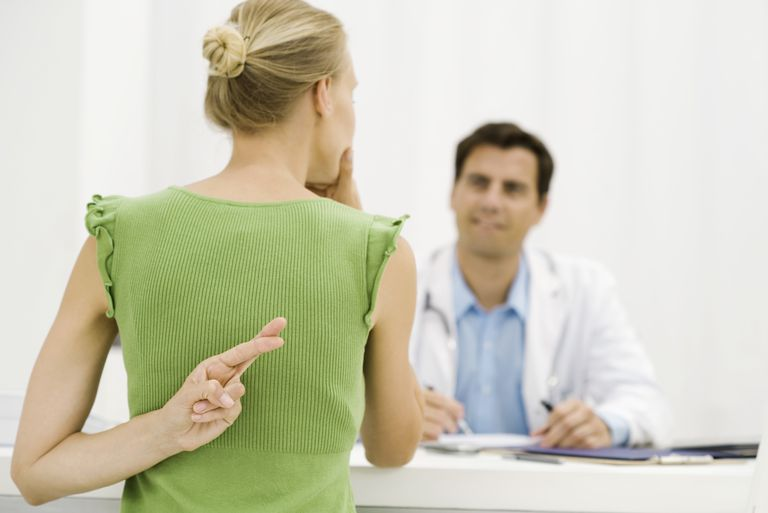 Woman crossing fingers in front of doctor