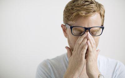 Blonde man rubbing eyes under eyeglasses