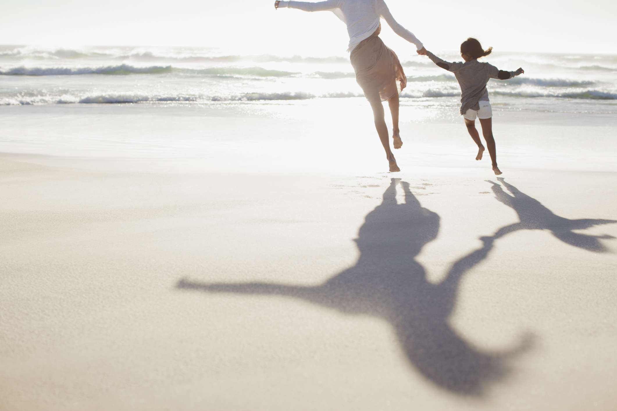 Woman and child running on the beach