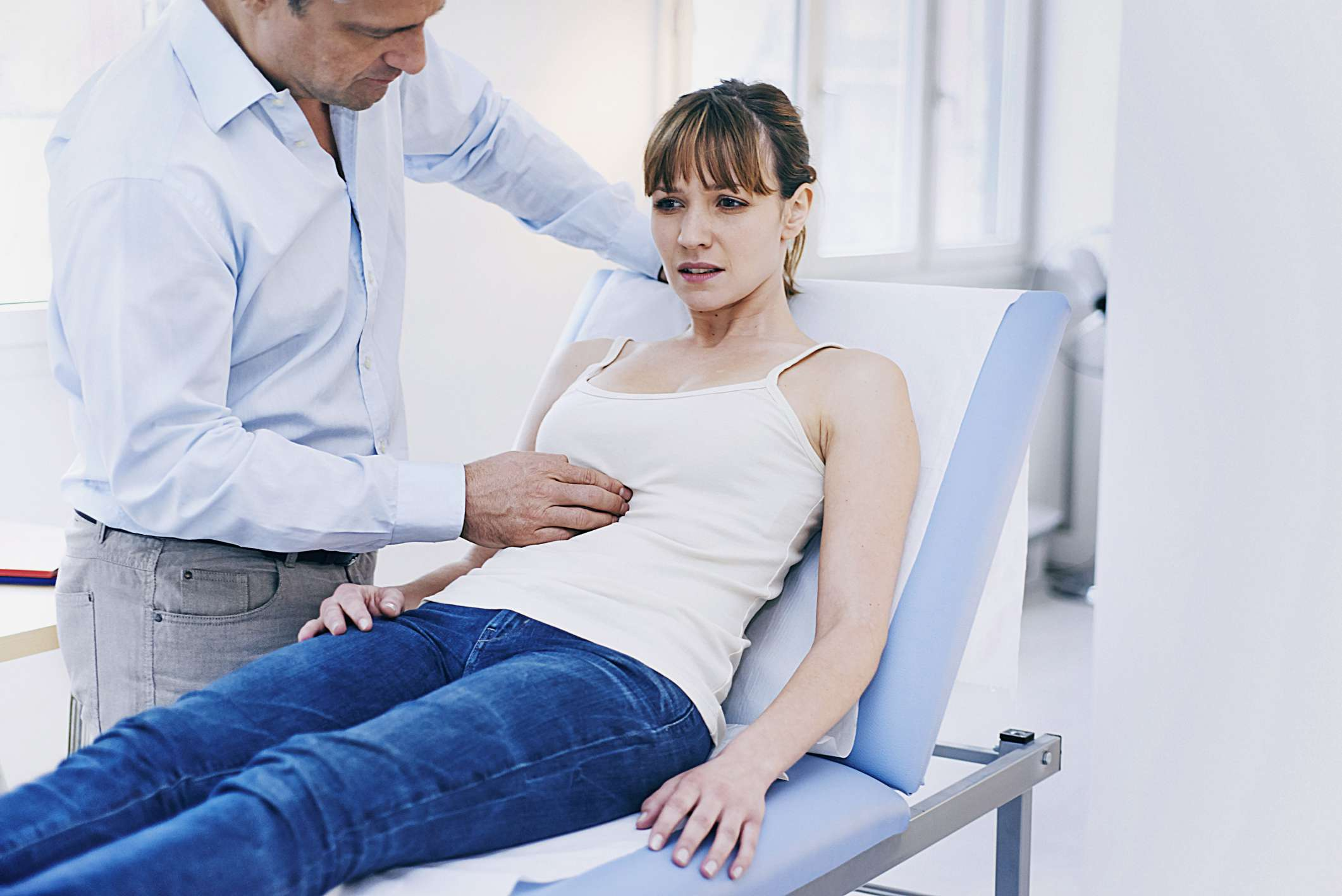 A woman getting her abdomen check by her doctor