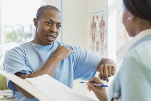 Man describing shoulder pain to doctor