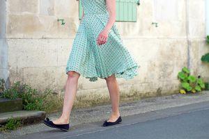 Woman in a skirt walking on a street.