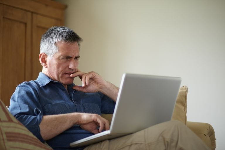 Confused man using laptop on couch
