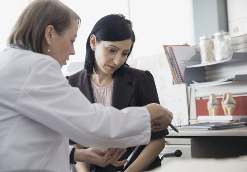 Woman reviewing medical records with her doctor