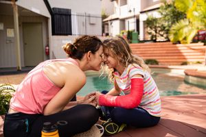 Mother and injured daughter in cast meditate at pool